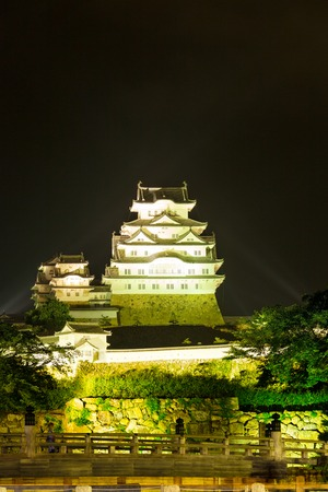 rampart: Traditional old wooden bridge, stone wall rampart at centered front of floodlight illuminated Himeji-jo castle at night in Himeji, Japan after 2015 renovations finished. Vertical
