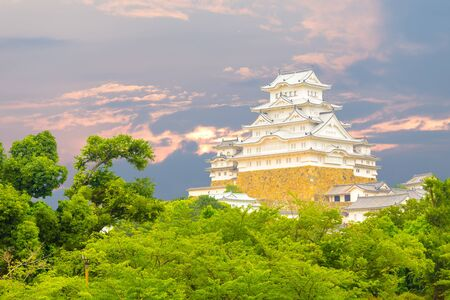 renovated: Beautiful sunset behind recently renovated Himeji-jo castle over the tops of trees seen from a distance in Himeji, Japan after 2015 renovations finished