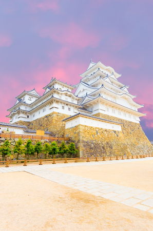 Himeji-jo castle on its high stone base and wide front courtyard on a sunset evening in Himeji, Japan post 2015 renovations completed. Angled vertical copy space