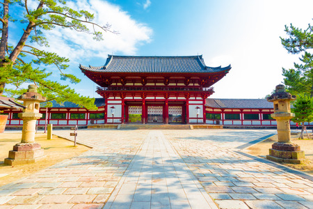 centered: Centered red gate ro-mon front entry to Todai-ji, Todaiji, temple and walkway housing the Daibutsuden on a bright sunny blue sky morning in Nara, Japan. Horizontal copy space
