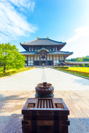 todaiji: Incense burner at head of path leading to Daibutsuden, Great Buddha Hall, at Todai-ji temple complex on a beautiful blue sky morning empty of tourists in Nara, Japan. Vertical copy space