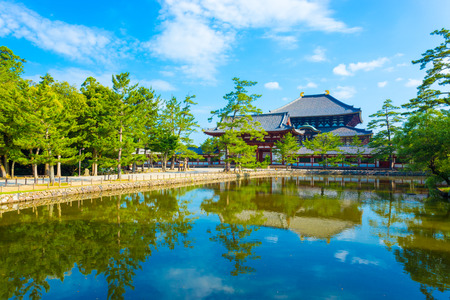 lake front: Pedestrian path and tranquil lake reflecting the front red entrance gate to Daibutsuden seen in distance on beautiful, sunny blue sky morning at Todai-ji temple in Nara, Japan. Horizontal copy space Editorial