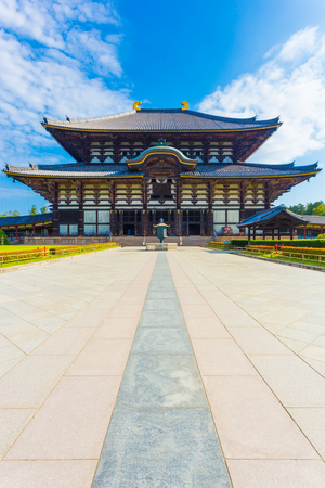 todaiji: Wide path leading to front exterior facade of Great Buddha Hall, Daibutsuden, nobody present, on sunny, blue sky morning in Todai-ji temple empty of people in Nara, Japan. Vertical copy space
