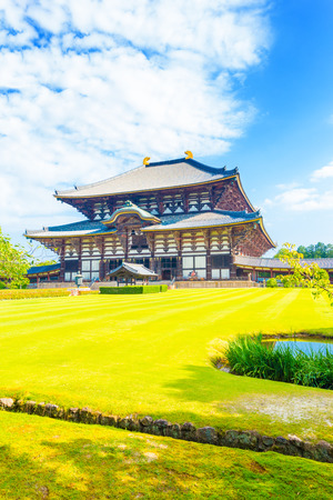 todaiji: Green grass in the wide lawn in front of entrance facade on grounds of main Great Buddha Hall, Daibutsuden, on a beautiful, blue sky summer morning at Todai-ji temple in Nara, Japan. Vertical