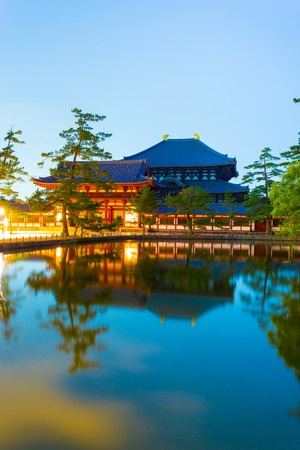haunting: Haunting long exposure of front entry gate and Daibutsuden Great Buddha Hall reflected in a still pond at night in Todai-ji temple in Nara, Japan