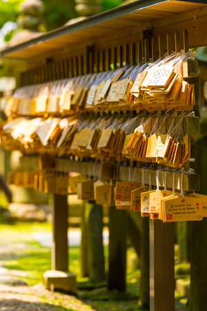 ema: Many small signs or plaques called wooden ema tags carrying written visitor messages and wishes hanging in front of a shinto shrine at the Todai-ji temple complex in Nara, Japan. Vertical