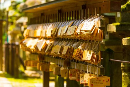 ema: Many small signs or plaques called wooden ema tags carrying written visitor messages and wishes hanging in front of a shinto shrine at the Todai-ji temple complex in Nara, Japan. Horizontal