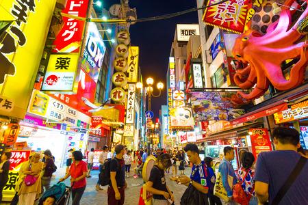 personas en la calle: OSAKA, JAPAN - JUNE 23, 2015: Tourists walking around pedestrian walking street at Dotonbori arcade under the iconic oversized octopus and night light signs in Namba district of Osaka, Japan