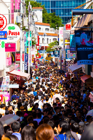 Harajuku: TOKYO, JAPAN - JUNE 26, 2016: Takeshita street lined with shops and crowded with young teenagers shopping, browsing and hanging out during the day in Harajuku. Vertical