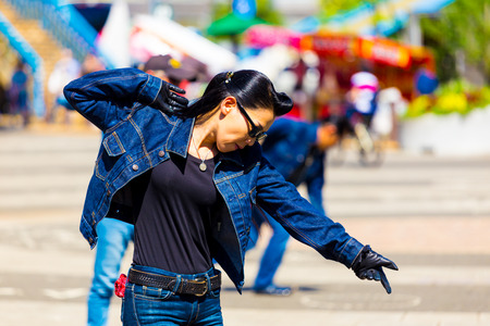 slicked: TOKYO, JAPAN - JUNE 26, 2016: Female rockabilly dancing in full jean outfit and slicked back hair performs to rock and roll music weekly at Yoyogi park