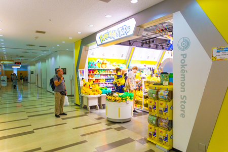 popularity: TOKYO, JAPAN - JULY 21, 2016: Caucasian tourists shopping at Pokemon Store at beginning of expolosive popularity as a result of the Pokemon Go game at a shop in Narita Airport. Horizontal Editorial
