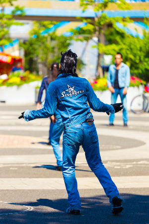 TOKYO, JAPAN - JUNE 26, 2016: Rear of rockabilly dancing man in full jean outfit and slicked back hair performs to 50s rock and roll music weekly at Yoyogi park Editorial