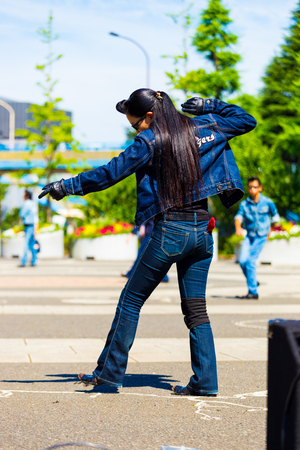slicked: TOKYO, JAPAN - JUNE 26, 2016: Rear of female rockabilly dancer in full jean outfit and vintage hairdo dancing to rock and roll music weekly at Yoyogi park