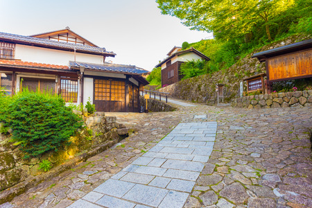 restored: Restored wooden buildings on inclined hilly stone path leads to entrance of Magome town on ancient Magome-Tsumago portion of Nakasendo trail in Kiso Valley, Japan. Horizontal Stock Photo