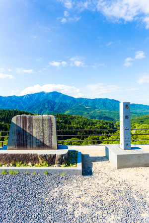 describes: Stone markers, left describes the joining of two prefectures, right marking elevation of Mount Ena stand at the viewpoint overlook above Magome on the Nakasendo route in Japan. Vertical Stock Photo