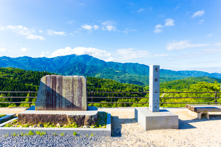 describes: Stone sign markers, left describes the joining of two prefectures, right marking elevation of Mount Ena stand at the viewpoint overlook above Magome on the Nakasendo route in Japan. Horizontal