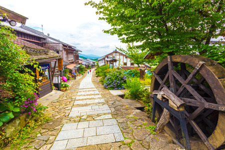 gifu: Magome, Japan - June 30, 2015: Japanese tourists visit a restaurant housed in restored wooden buildings on a traditional stone path on the ancient Magome-Tsumago portion of Nakasendo trail.