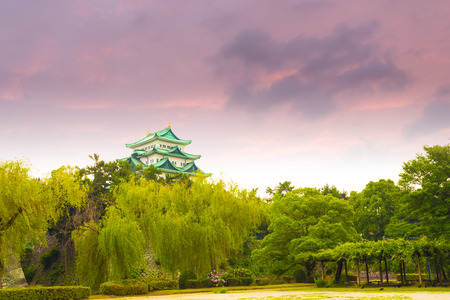 stronghold: Moody sunset clouds hover above Nagoya Castle stronghold over a green treeline in Japan Editorial