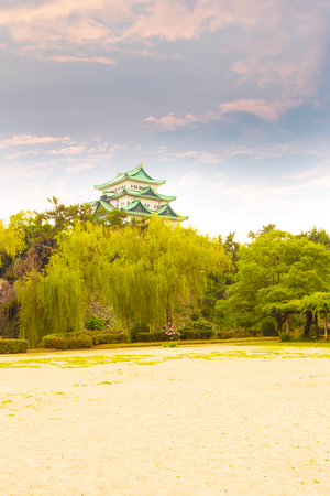 stronghold: Ancient Nagoya Castle stronghold above a green treeline on a colorful sunset sky evening in Japan. Vertical Editorial