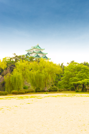 stronghold: Historic Nagoya Castle stronghold exterior from a distance above a green treeline on a clear blue daytime sky in Japan. Vertical