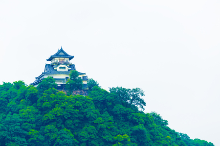 atop: Telephoto closeup facade of Inuyama Castle on overcast day atop hill forest in Gifu Prefecture, Japan. Horizontal copy space