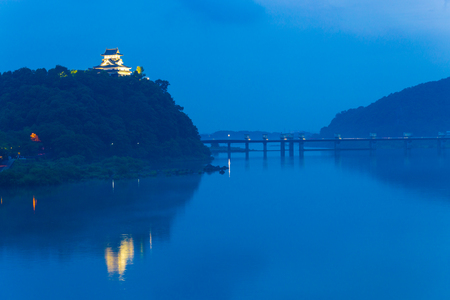 Near dark at far Inuyama Castle lighted by floodlights above the Kiso River at dusk in Gifu Prefecture, Japan