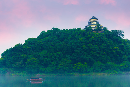 stronghold: Sunset sky above a tourist cruise boat on the Kiso River with Inuyama Castle stronghold atop a forest hill on a summer evening in Gifu Prefecture, Japan. Horizontal