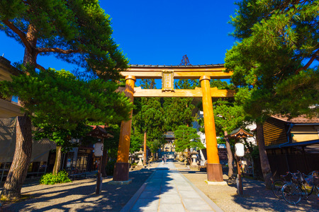 Large wooden torii gate entrance to Sakurayama Hachiman-gu Shinto Shrine on a clear blue sky day in Takayama, Hida Prefecture, Japan. Horizontal