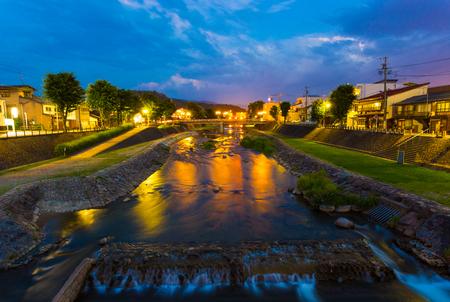 thru: Beautiful blue hour twilight sky along the Miya-gawa river flowing thru the center of Takayama city, a tourist travel destination in Gifu prefecture, Japan at night. Horizontal Stock Photo