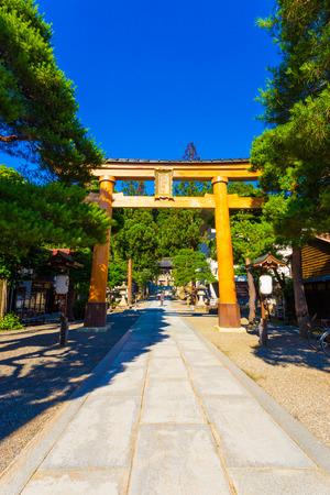 Wooden torii gate entrance to Sakurayama Hachiman-gu Shinto Shrine on a clear blue sky day in Takayama, Hida Prefecture, Japan. Vertical