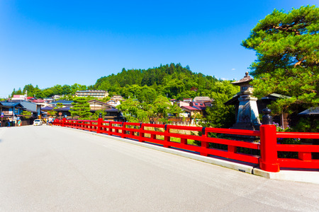 gifu: The bright red Naka-Bashi bridge marks the entrance to historic old town, a tourist destination in the mountain city of Hida-Takayama in Gifu Prefecture, Japan at daytime. Horizontal Stock Photo