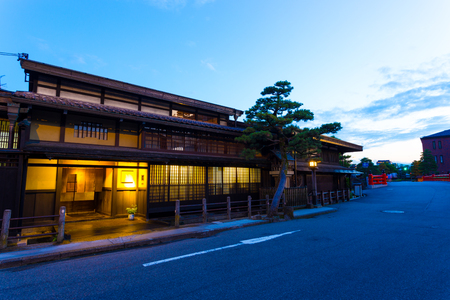 gifu: Modern street runs over Naka-bashi bridge in front of traditional Japanese wooden homes lighted at evening dusk in historic old town of Hida-Takayama in Gifu Prefecture, Japan. Horizontal