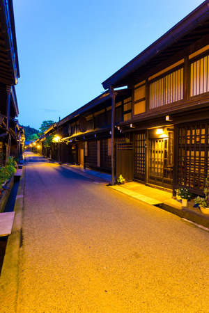 night dusk: Takayama, Japan - July 10, 2015: Traditional Japanese dark wooden homes, restaurants lighted at night line empty pedestrian street in Kamisannomachi district of historic old town at dusk. Vertical Editorial