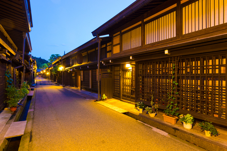 hida: Takayama, Japan - July 10, 2015: Traditional Japanese dark wooden buildings illuminated at night line pedestrian street in Kamisannomachi district of historic old town. Vertical Editorial