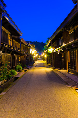 illuminated: Takayama, Japan - July 10, 2015: Kamisannomachi street centered is home to old town lined with rows of beautiful traditional dark wooden houses and sake brewery at dusk. Horizontal