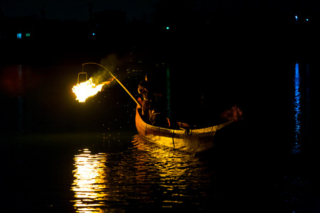 Inuyama, Japan - July 5, 2015: Night fire is used to help cormorant bird catch fish in a traditional form of Japanese fishing, ukai by firelight on Kiso River in Gifu Prefecture