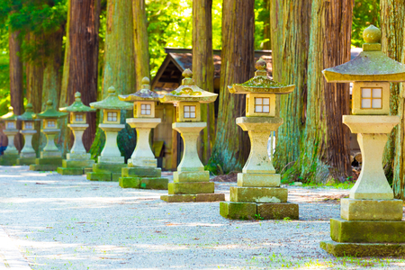 Medium sized traditional Japanese Stone Lanterns lined up in a row to vanishing point on a shaded path leading to a temple in Takayama, Japan