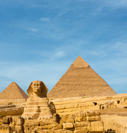 front facing: Front facing Sphinx and the large Egyptian Pyramids of Khafre, Menkaure slightly offset in front of blue sky in Giza, Cairo, Egypt. Lots of copy space Stock Photo