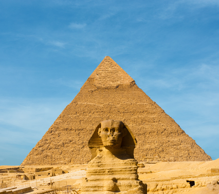 The Great Sphinx face forward centered in front of the largest Egyptian Pyramid of Khafre in Giza, Cairo, Egypt on a blue sky day. Lots of copy space