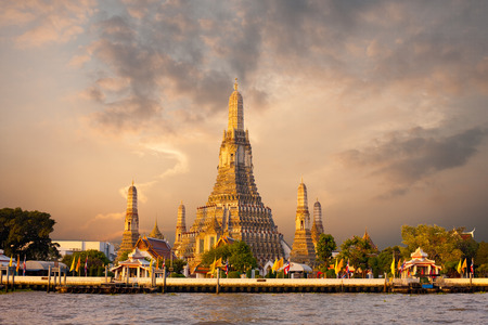 chao phraya: The iconic Temple of Dawn, Wat Arun, along the Chao Phraya river with a colorful red sky at morning sunrise in Bangkok, Thailand