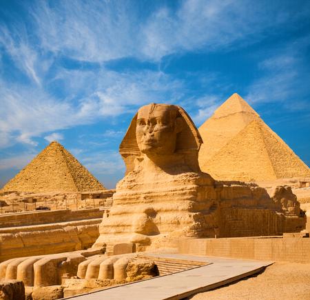 Egyptische Sfinx full body portret met hoofd, voeten met alle piramides van Menkaure, Chefren, Khufu in de achtergrond op een heldere, blauwe hemel dag in Giza, Egypte leeg met niemand. exemplaar ruimte