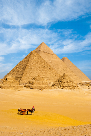 egyptian pyramids: A group of tourists dismount their horse cart to view all the Egyptian pyramids together on a wispy cloudy day in Giza, Cairo, Egypt. Vertical copy space