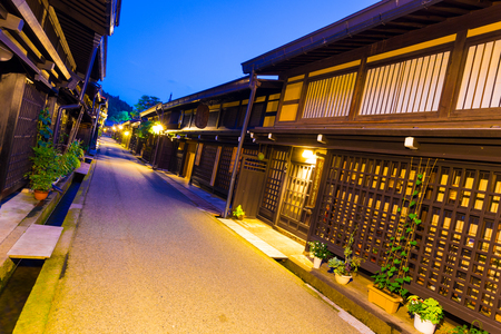Takayama, Japan - July 10, 2015: A row of traditional wooden houses line a street in old town neighborhood of Hida-Takayama, Gifu, Japan. Tilted wide angle perspective with embedded GPS coordinates