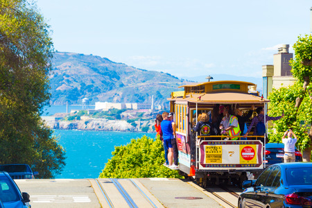 san: San Francisco, USA - May 15, 2016: Cable car with tourists riding outside approaching steep precipice edge at peak of Hyde St with amazing view of Alcatraz Prison, bay water on sunny blue sky day