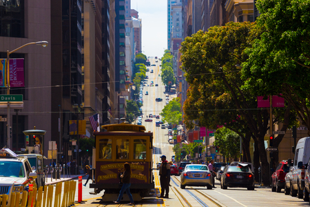 downtown district: San Francisco, USA - May 9, 2016: Cable car looking straight uphill at steep California Street in the financial district of downtown on a sunny day. Compressed using telephoto lens Editorial