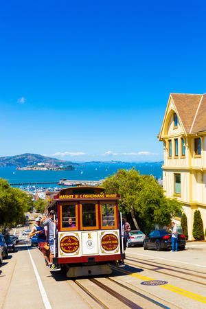 alcatraz: San Francisco, USA - May 15, 2016: Tourists riding outside cable car climbing steep uphill street on Hyde St with view of Alcatraz Prison and Victorian house on blue sky day. Vertical. Copy space Editorial