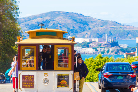 steep: San Francisco, USA - May 15, 2016: Iconic approaching cable car full of tourists at the top peak of Hyde Street hill overlooking Alcatraz Island with sweeping nature views of the bay and Marin Editorial
