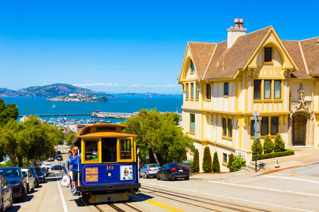 alcatraz: San Francisco, USA - May 15, 2016: Blue cable car with hanging tourists going uphill on steep Hyde St with sweeping view of Alcatraz Prison, bay water and yellow Victorian house on sunny blue sky day Editorial