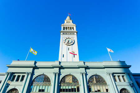centered: Day front facade view of centered Ferry Building and clock tower looking up from a low angle on a sunny, clear blue sky day in San Francisco, California. Horizontal Stock Photo