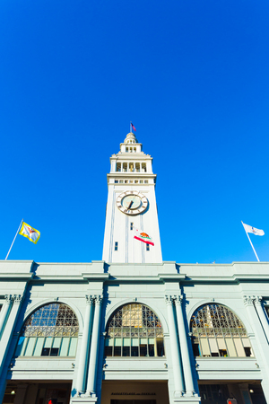 centered: Daytime front facade of centered Ferry Building and clock tower looking up from a low angle on a sunny, clear, blue sky day in San Francisco, California. Vertical